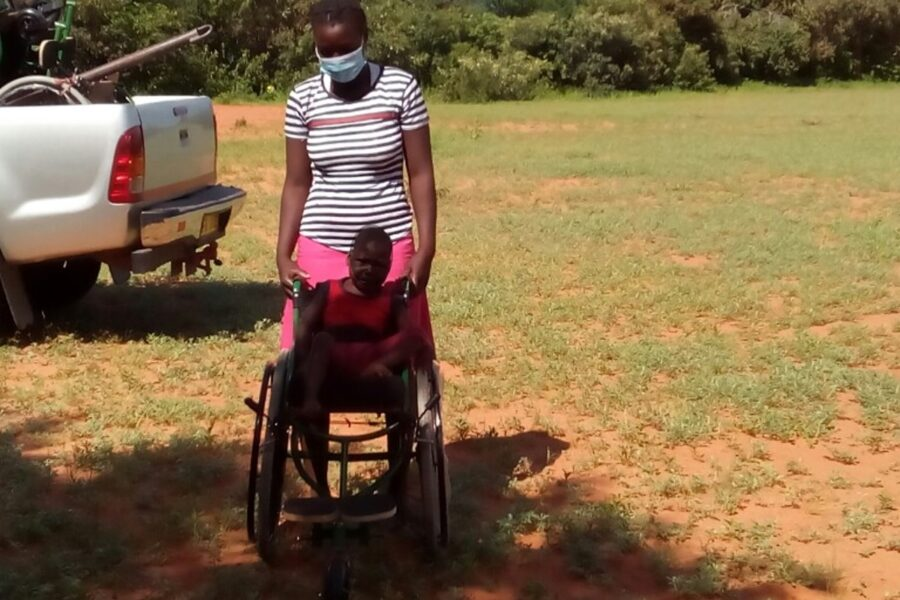 Photo of Loveness with her Child seated in a wheelchair in front of her