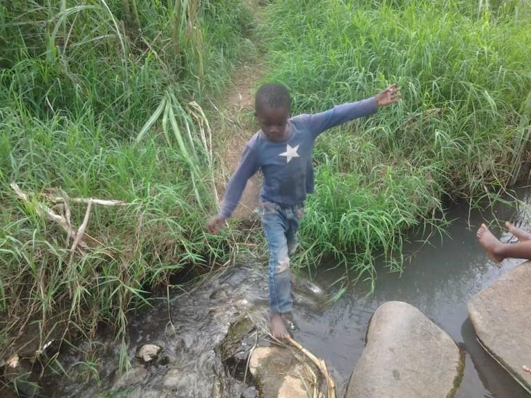 Young boy playing around a burst sewage gutter at Ward 17 Hobhouse, Mutare, Zimbabwe